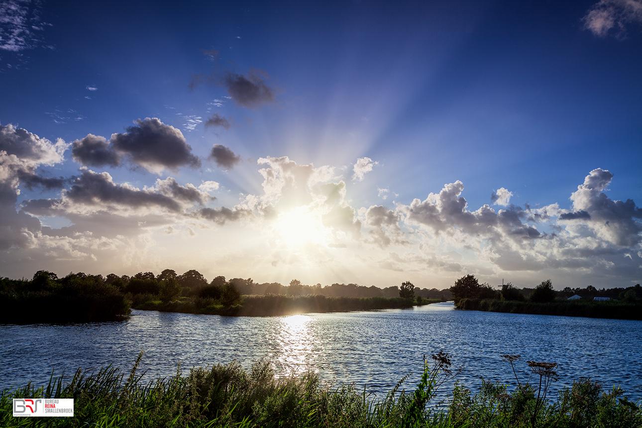 Zonnestralen vanachter de wolken vandaan over het water in Schipsloot Roderwolde Drenthe